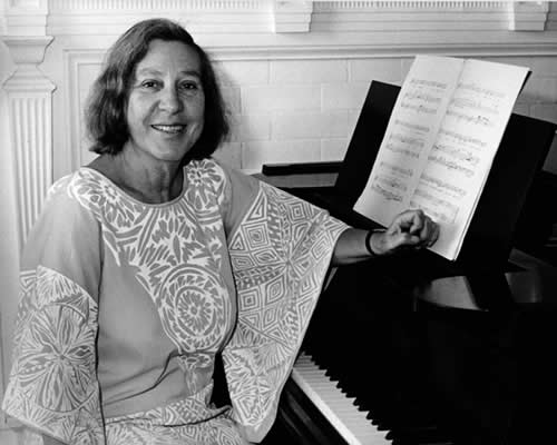 Vivian Fine seated at a piano
